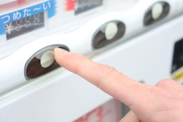 ジュースの自販機のボタンを押す指