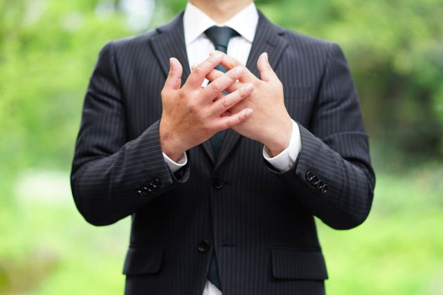 胸の前で手を重ねるスーツ姿の男性