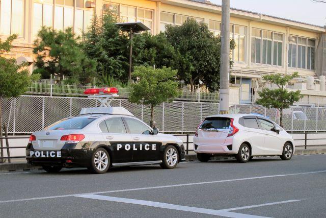 交通違反の取り締まりでパトカーに止められた白い車